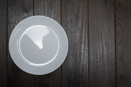 faience: white plate on dark wooden background