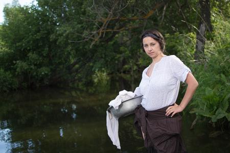 campesino: campesina lava la ropa en el río cerca del bosque