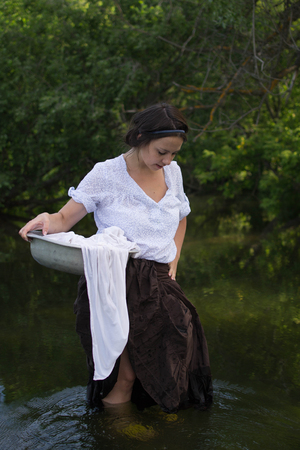 campesino: peasant woman washes clothes in the river near the forest