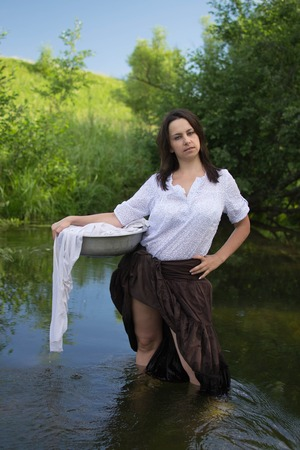 peasant: peasant woman washes clothes in the river near the forest