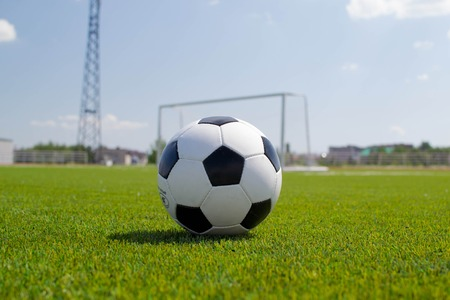 soccer ball on a green lawn on the background of the stadium
