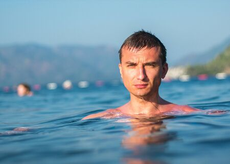 Cute guy swims in the sea on a sunny day