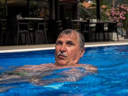 Joyful man swimming in the pool in the summer Banque d'images