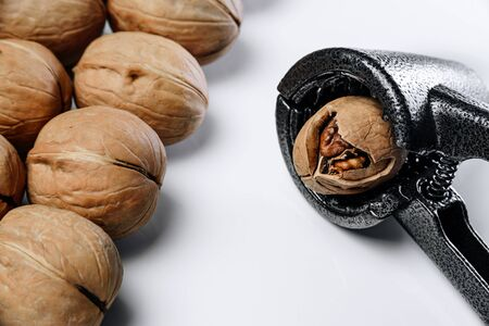 Walnuts on a white background. Nearby lies a nutcracker.