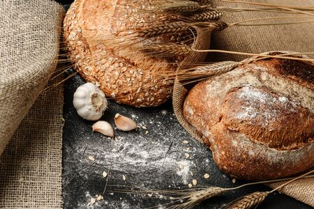 Flat lay composition with a rustic dough lying on a black flour-strewn surface with a knife, garlic, rolling pin, sackcloths and ears of wheat. The concept of a rural bakery.