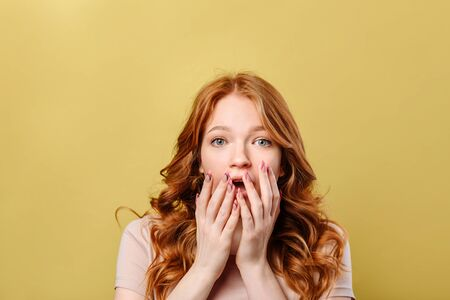 Astonished young woman put her palms to her mouth, looking at the camera and standing isolated on a yellow background.