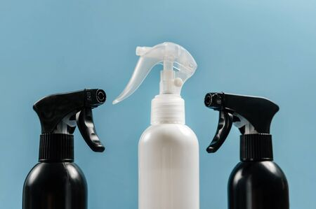 Spray guns with cleaning agent close-up on a blue background. The concept of cleanliness and order in the house.
