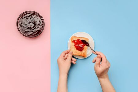 Female hands spread bread toast with jam next to a jam dish on a pink and blue background with a copy space.