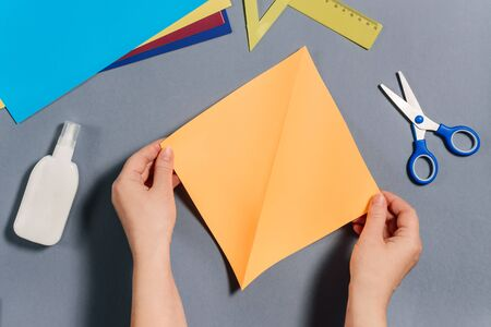 We make a fish out of colored paper. Hands are holding a square sheet of paper. DIY concept. Step by step instructions for children. Step 2.