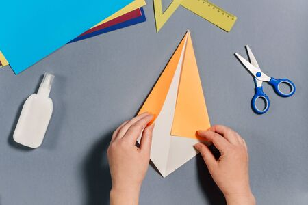 We make a fish out of colored paper. Hands are folding paper. DIY concept. Step by step instructions for children. Step 3.