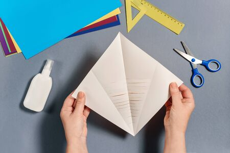 We make a fish out of colored paper. Hands hold a blank for gluing. DIY concept. Step by step instructions for children. Step 5. Фото со стока