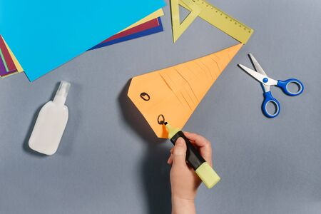 We make a fish out of colored paper. Hand with marker draws an eye. DIY concept. Step by step instructions for children. Step 7. Фото со стока