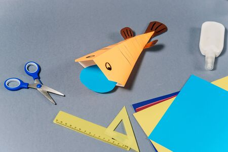 We make a fish out of colored paper. The finished toy lies on the table. DIY concept. Step by step instructions for children. Step 8. Фото со стока