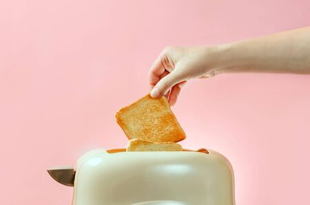 A female hand takes out a piece of toasted bread from a toaster on a pink background with a copy space. Light breakfast concept.