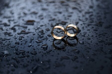 Two wedding rings on a smooth surface with water drops. Wedding concept with selective focus. 免版税图像