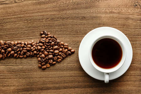 Arrow-shaped coffee beans indicate a cup of coffee. Flat lay composition with a cup of coffee and grains of roasted coffee on a wooden background.