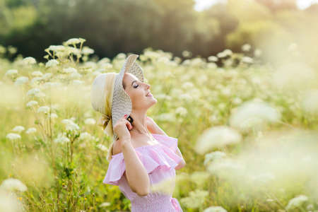 A girl in a straw hat is resting in nature. A young woman smiles, raising her face to the sun. Summer vacation concept.