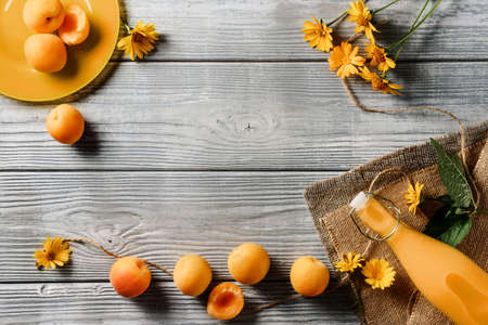 Food frame with apricots, a bottle of juice and yellow flowers on a wooden background with copy space. Archivio Fotografico