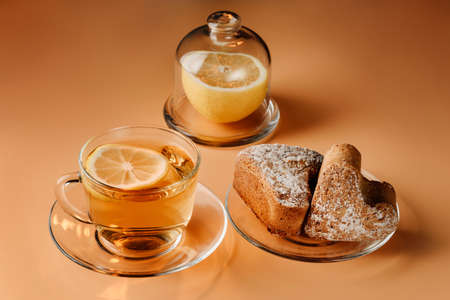 Tea with lemon, curd muffins and lemon on a light background. Light breakfast concept. Reklamní fotografie