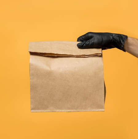 A man's hand in a black protective glove holds a paper bag for food delivery on a yellow background. Fast food safe service concept.