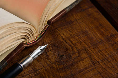 An antique fountain pen close-up next to an open book on a wooden textured table. Composition with pen and book with selective focus.