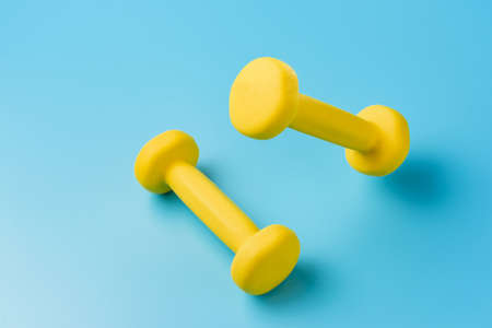 Two yellow dumbbells on a blue background.