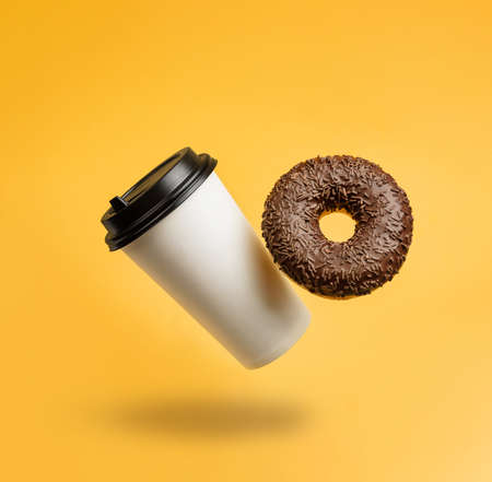 A glass with coffee and a chocolate donut levitating against a yellow background with a copy space.