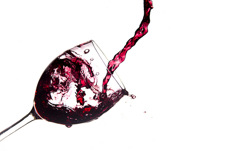 Glass of spilled wine splashing out