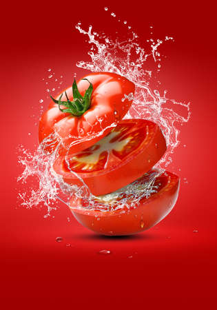 Floating tomato cut with splashes of water. Creativity in the kitchen Zdjęcie Seryjne