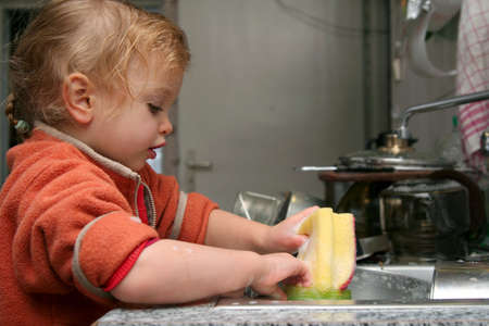 Little  washing the dishes in the kitchen photo