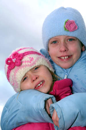 Happy children in winter outfit  on a blue sky background. Stock Photo - 740216