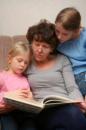 Grandmother sitting on the armchair with her grandchildren and reading photo