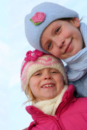 Happy children in winter outfit  on a blue sky background. photo