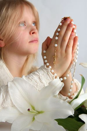 Little blond girl counting the rosary