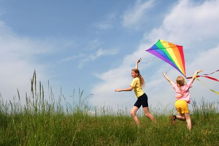 Los niños de vuelo arco iris cometa en el prado en un cielo azul de fondo
