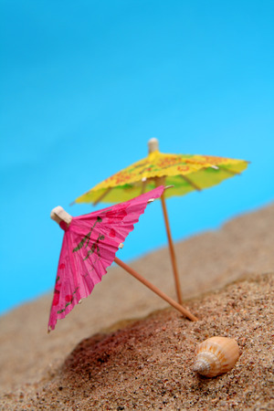 Colorful paper  umbrellas in the sand on a blue background Stock Photo