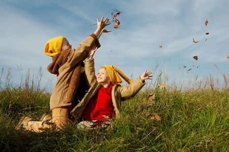 Children wearing yellow caps  playing on autumnal meadow