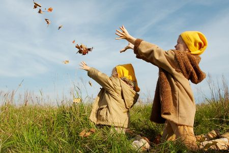Children wearing yellow caps  playing on autumnal meadow photo