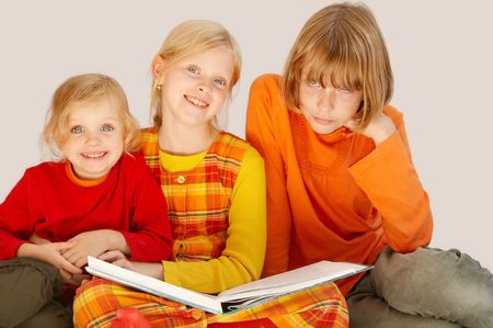 Young pretty sisters   reading a book together photo