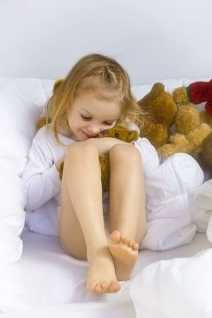 Little blond girl wearing white blouse in white bedchlothes Stock Photo - 3200898