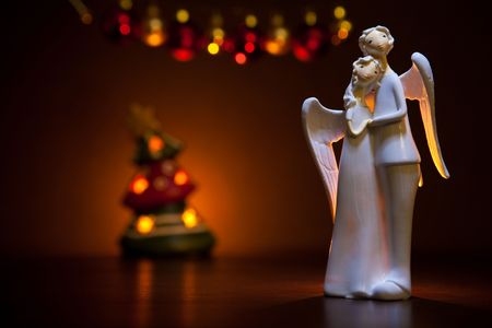 Two angels in front of christmas tree in the candle light Stock Photo