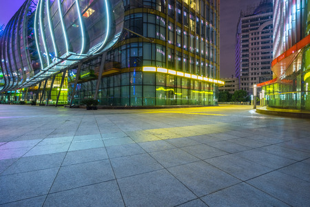 modern building and empty brick floor at night. Stock Photo