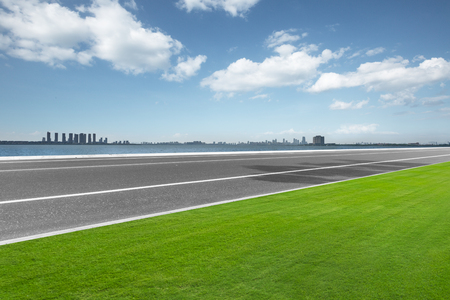 empty asphalt road and meadow with cityspace in blue sky Stock Photo
