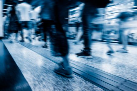 abstract blur of passengers rushing at subway station.