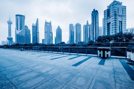 Empty brick floor with modern building in Shanghai, blue tone