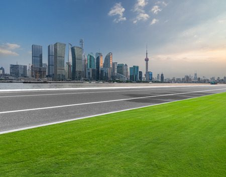 empty asphalt road and meadow with shanghai cityspace and skyline in blue sky Stock Photo
