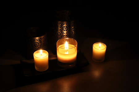 Many glass of scented aromatic candles are lighting in the dark living room during Christmas celebration party with happy family