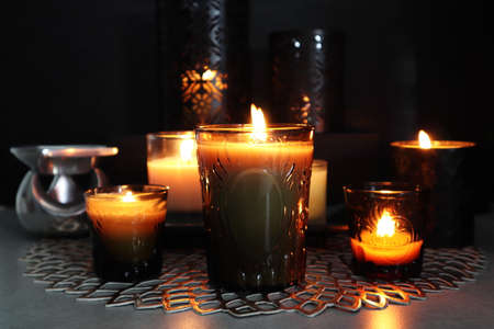 Many glass of scented aromatic candles are lighting in the dark living room during Christmas celebration party with happy family Imagens
