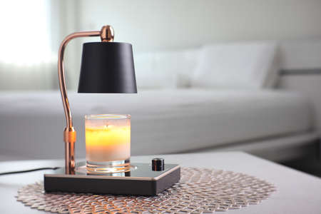 The luxury lighting aromatic scent glass candle is put on the electric lamp candle warmer heater on the grey table in the white bedroom Foto de archivo