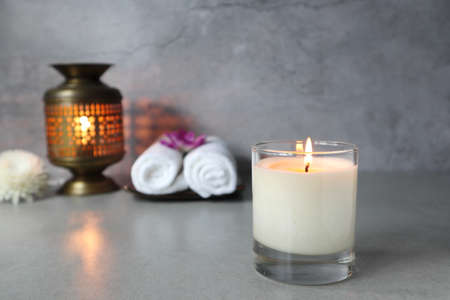 The luxury lighting aromatic scented ivory colour glass candle lighting display on the grey table with spa towels cloth and essential oil aroma brass burner on cement wall background in luxury spa